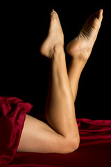 woman legs and a red sheet feet kicked up side lit