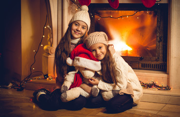 Toned photo of two happy girls sitting with toy at fireplace on
