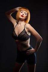 Languorous red-haired woman posing at camera