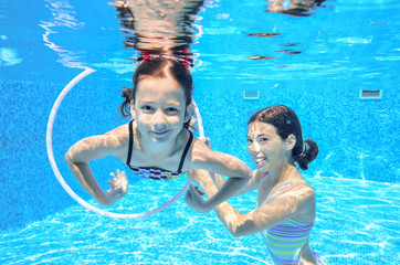 Happy active kids swim in pool and play underwater having fun