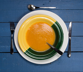 plate of pumpkin soup on a blue wooden table
