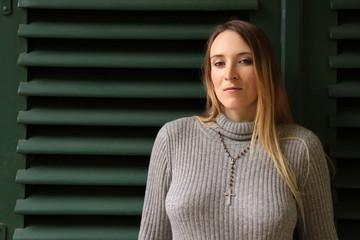 Vollbusige Frau im Pullover mit Rosenkranz