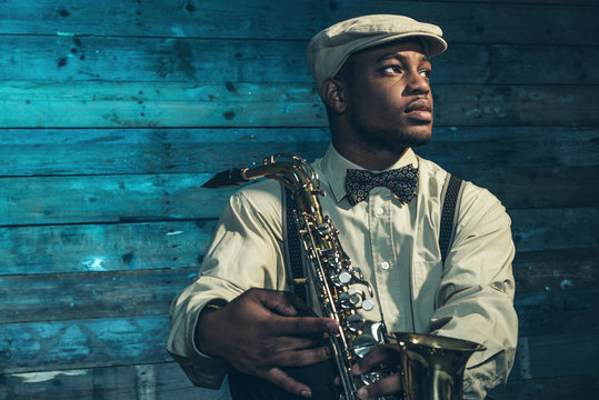 African american jazz musician with saxophone in front of old wo
