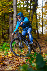 Extreme cyclist riding on mountain bike in autumn forest
