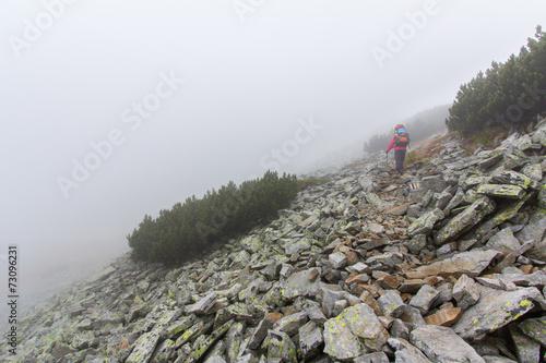 Wall mural Backpacker walking mountain slope in fog. Pirin, Bulgaria.