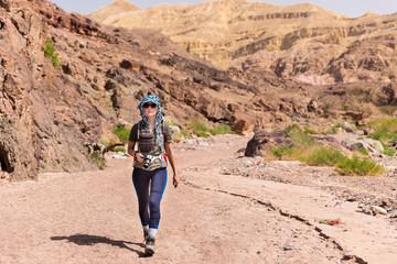 Woman photographer walking desert canyon.