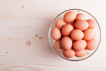 brown eggs in a large glass bowl on a light wooden table view