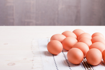 brown eggs arranged randomly on the right side on a light wooden