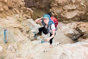 Wall Mural - Woman climbing rock gorge.