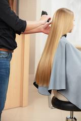 Blonde hair. Hairdresser combing long blonde hair in salon