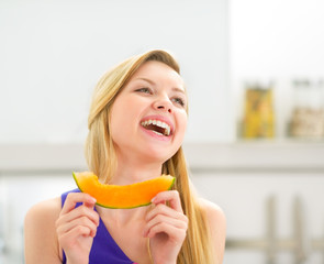 Portrait of happy young woman with melon slice