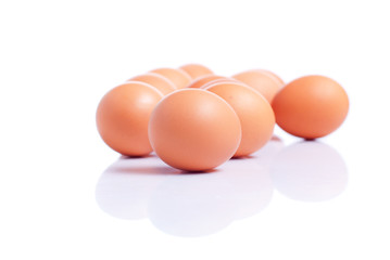 some brown eggs one in the foreground on a white isolated backgr