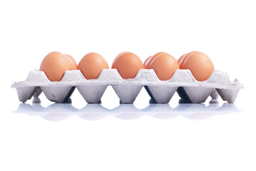 many brown eggs laid in a tray isolated on white background with