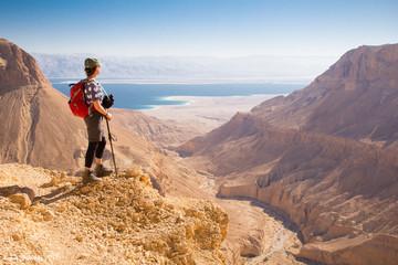 Backpacker woman standing desert mountain edge. Wall mural