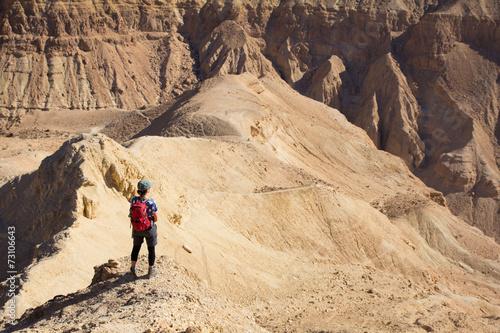 Wall mural Woman standing desert mountain peak ridge.