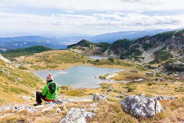 Wall Mural - Woman tourist sitting above mountain lake. Seven Lakes, Bulgaria