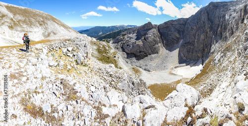 Wall mural Woman backpacker standing above deep canyon glacier