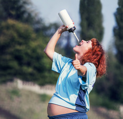 Active pregnant woman drinking water