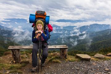 Wall Mural - Woman backpacker sitting mountain bench.
