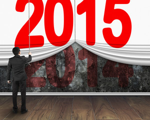 businessman pulling down 2015 curtain to cover old dark 2014