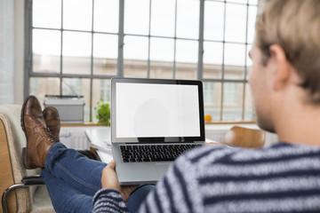 junger mann schaut auf seinen laptop