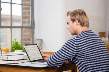 junger mann lernt zuhause am laptop