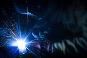 Employee welding structures with sparks