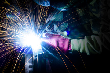Employee welding steel structures with sparks.
