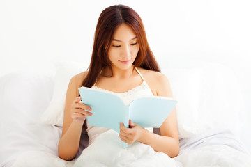 beautiful young Woman lying in bed while reading a book