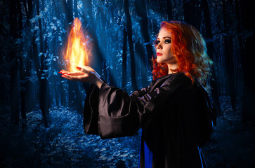 Fototapete - Witch in the night forest holds fire