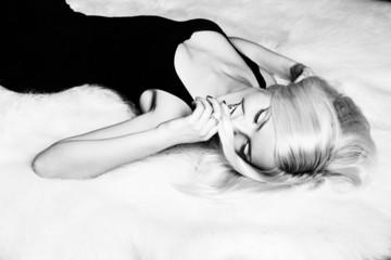 beautiful women a smile lying on white carpet in a black dress