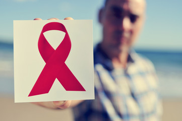 young man with a picture of a red ribbon for the fight against A