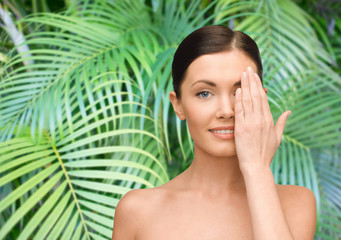 smiling young woman covering face with hand