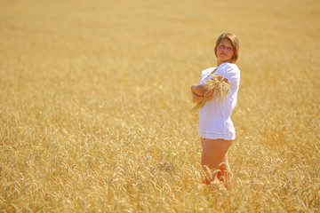 young woman posing in a field with wheat