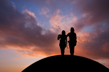 silhouetted couple standing on hill in sunset sky