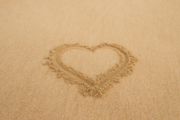 drawing a heart on wet golden beach sand