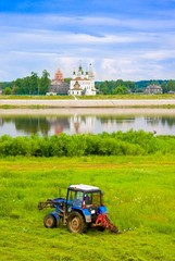 Farmer mowing against church and river, Russia