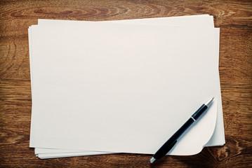 Ballpoint pen lying on sheets of paper