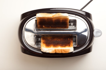 Black toaster, two burnt black slices of bread