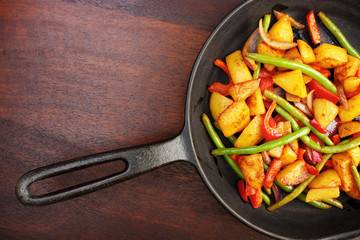 Fried vegetables on iron frying pan with copyspace