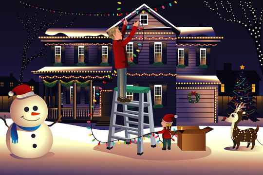Father son putting up lights around the house for Christmas