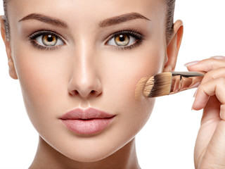 woman applying liquid tonal foundation  on the face