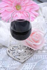 Wall Murals Flower shop glas rode wijn met roze bloemen en transparante stof