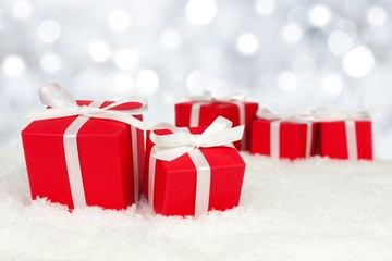 Red Christmas gift boxes in snow with twinkling background