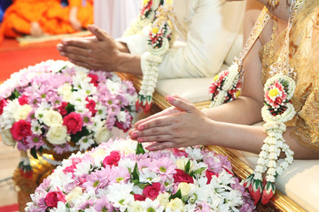 Hands pouring blessing water into bride's hands inThai ceremony.