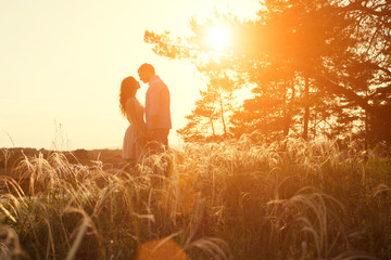 loving couple kissing at sunset