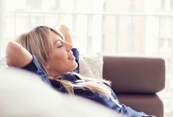 Relaxed young woman lying on couch Fotomurais