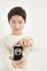 Asian young man taking photo by digital camera