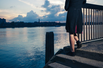 Woman stranding on stairs by river