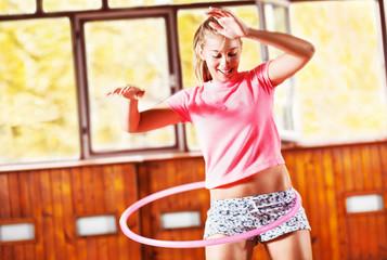 Girl spinning hula hoop, indoor.